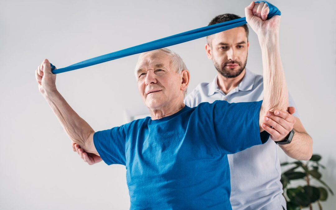 focused homecare therapist assisting senior man exercising with rubber tape